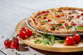 Pizza with green leaves on brown wooden plate