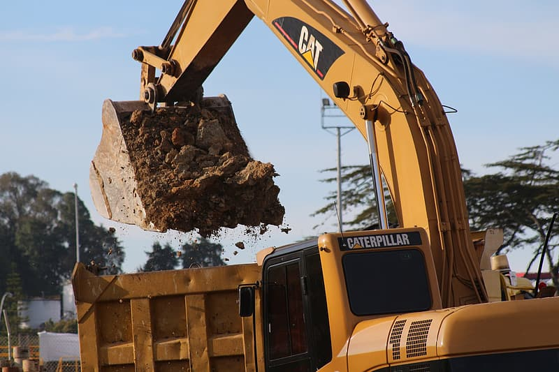 Yellow Caterpillar excavator bucket filled with soil above yellow dump truck at daytime