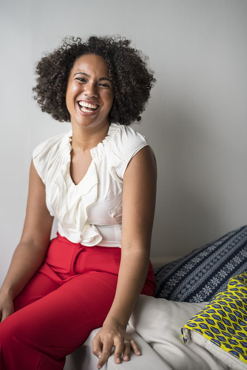 Woman in white sleeveless shirt and red pants sitting on bed