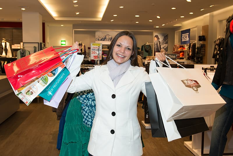 Woman in white coat holding paper bags