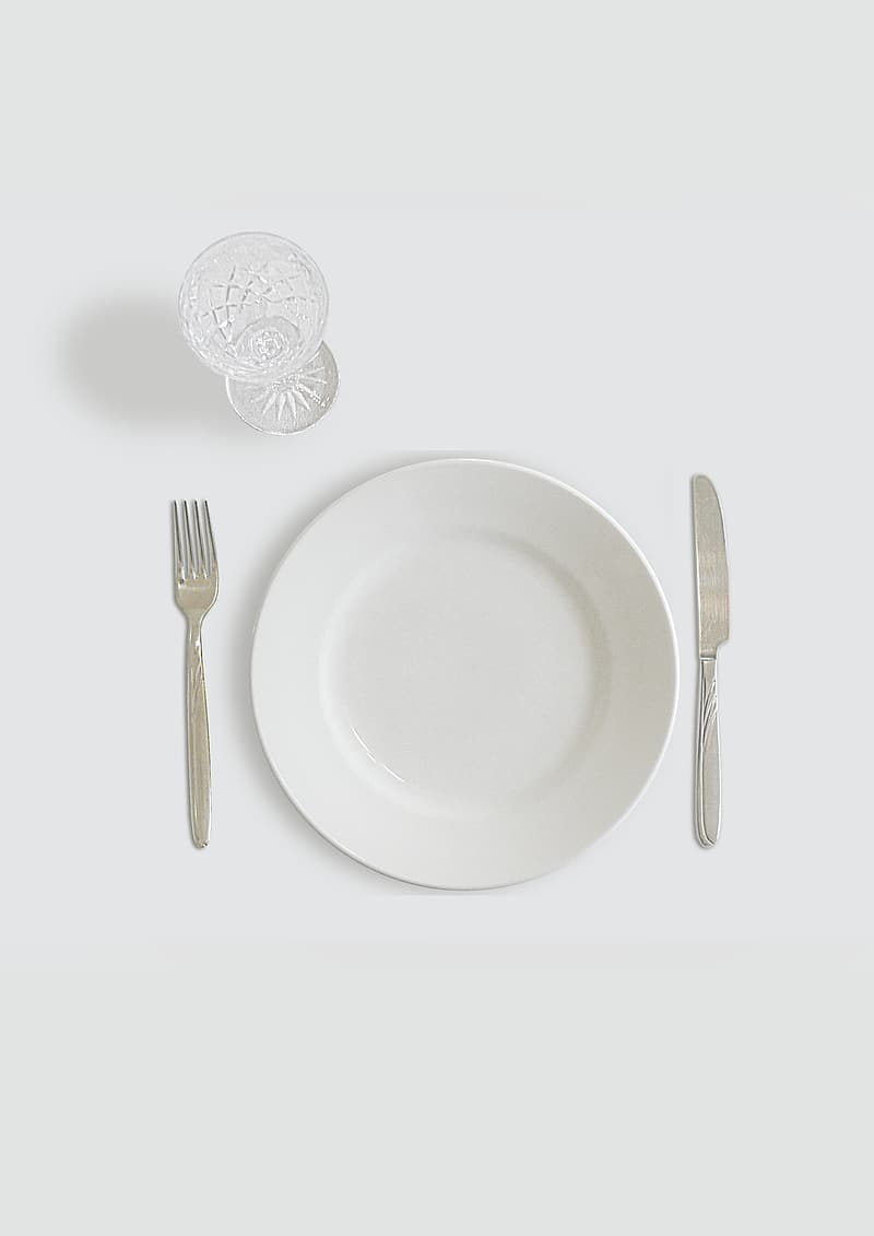 Round white ceramic plate beside butter knife and fork with clear footed glass