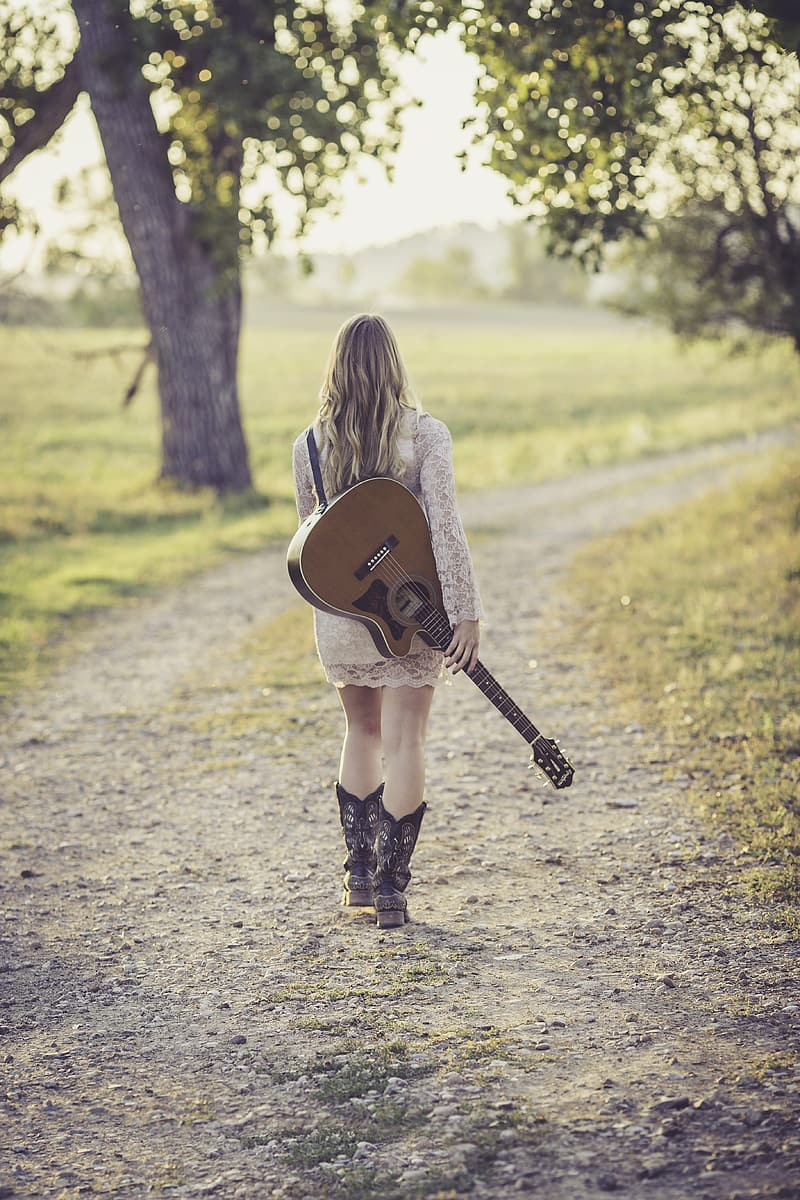 Walking woman holding brown guitar at daytime