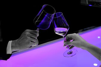Two person both holding clear wine glasses