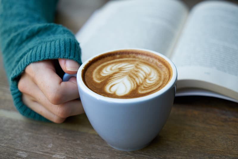 Person holding blue ceramic mug filled with coffee