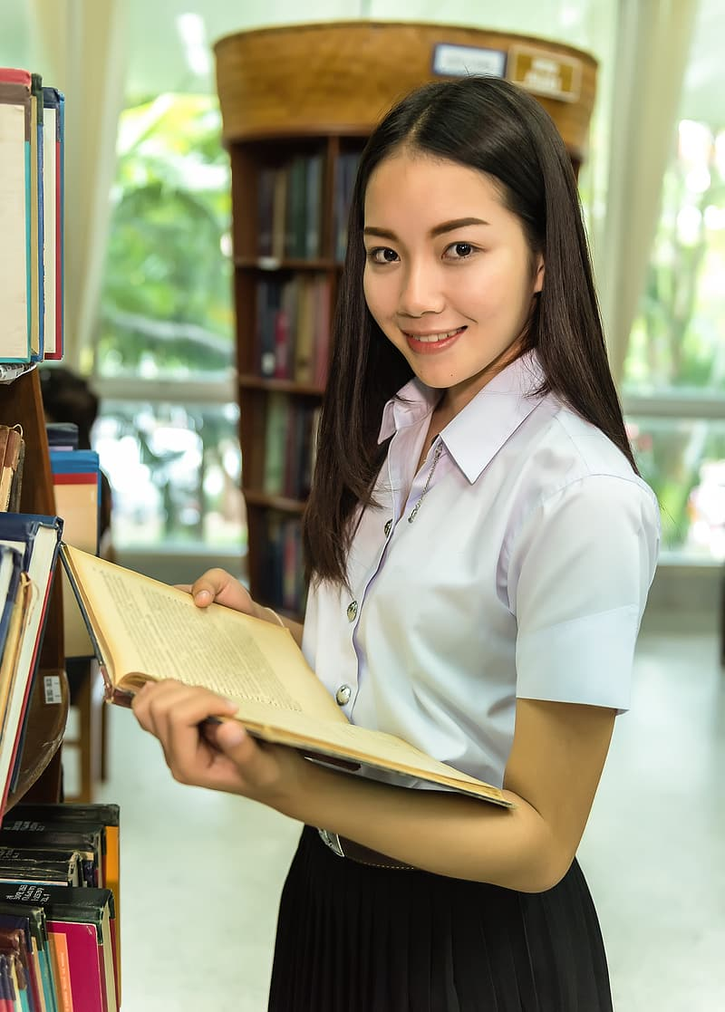 Woman in whiteblouse and black shirt holding book
