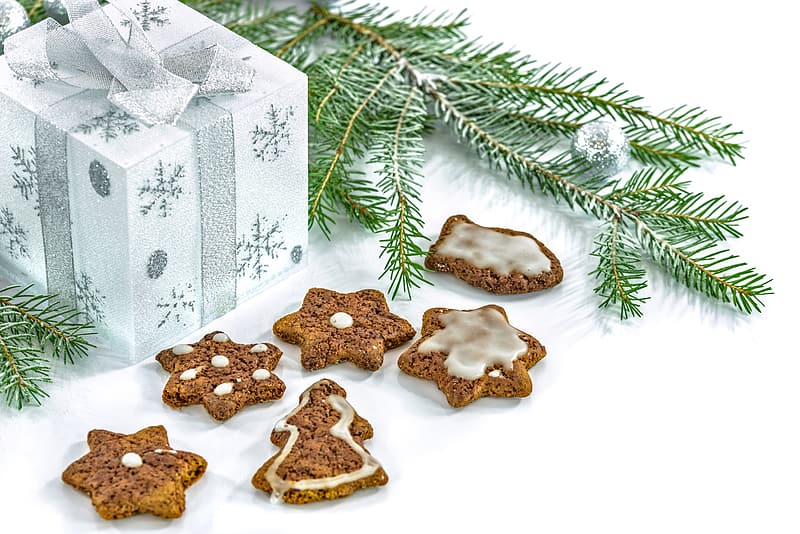Five assorted-shape baked cookies near white gift box