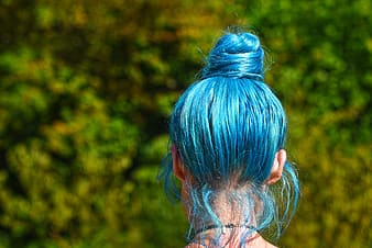 Blue haired woman in front of green leaves