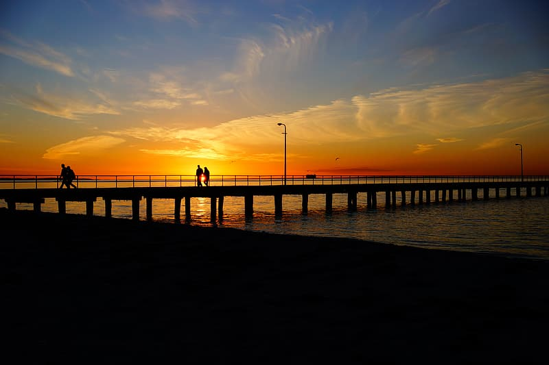 Silhouette of couple walking on sea dock during golden hour