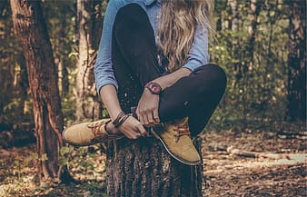 Girl in chambray dress shirt, black jean and brown boots sitting on tree log
