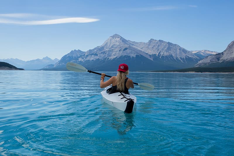 Woman in black and white dress sitting on white kayak on blue water during daytime