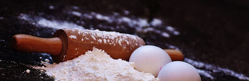 Brown wooden rolling pin and eggs