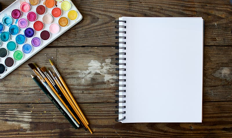 White notebook with pencils and pencils