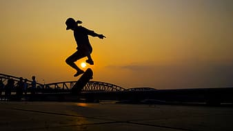 Silhouette photo of person skating during golden hour