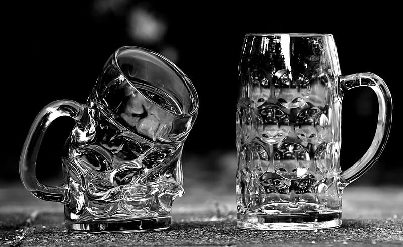 Two clear beer mugs on gray surface