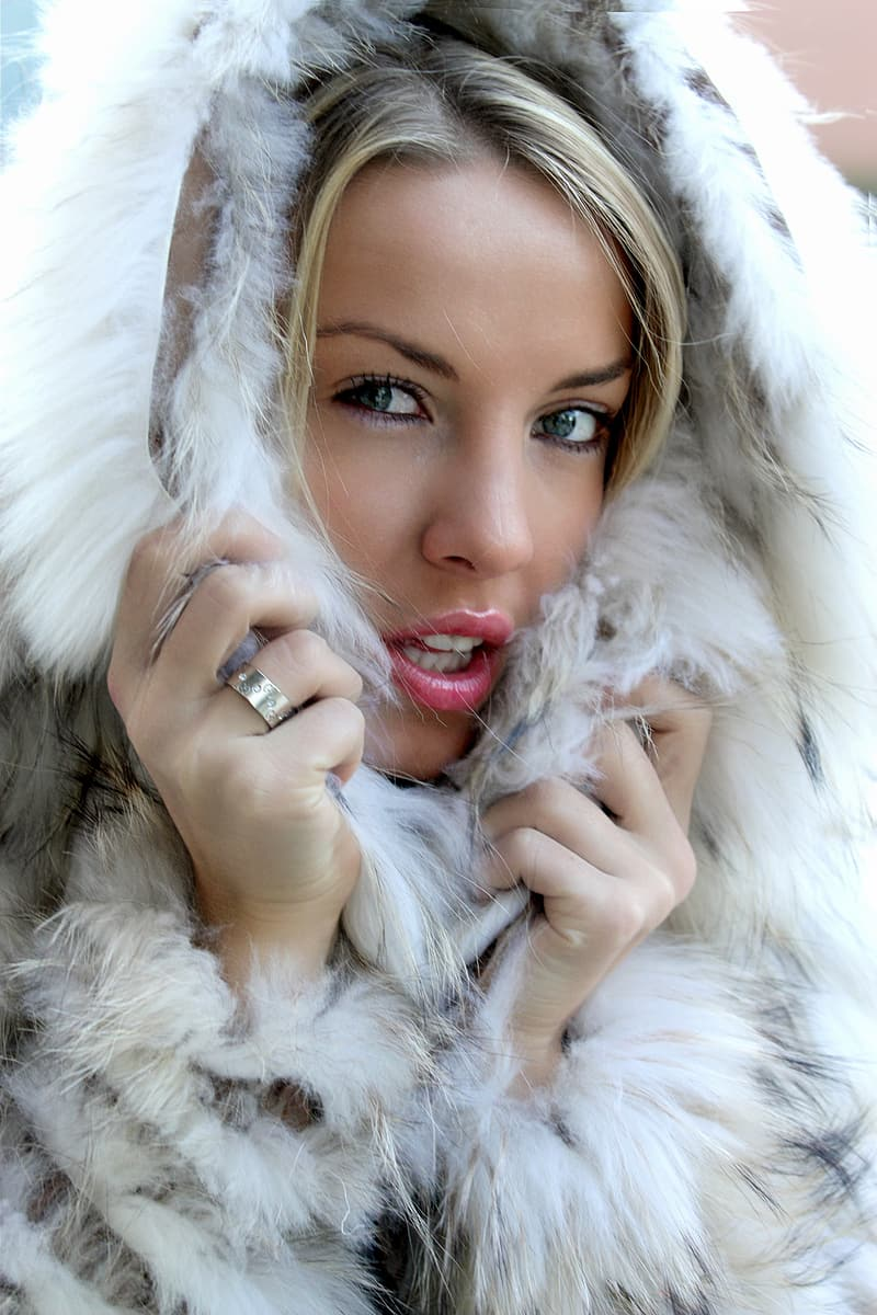 Woman holding white and black parka coat