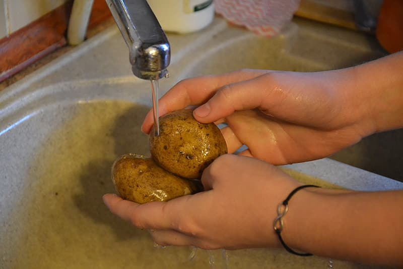 Person cleaning potatoes