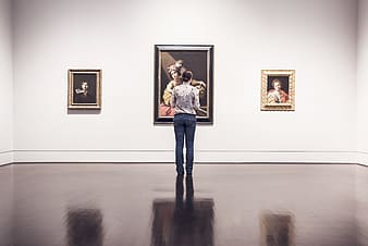 Woman standing in front of three paintings mounted on wall in well lit room