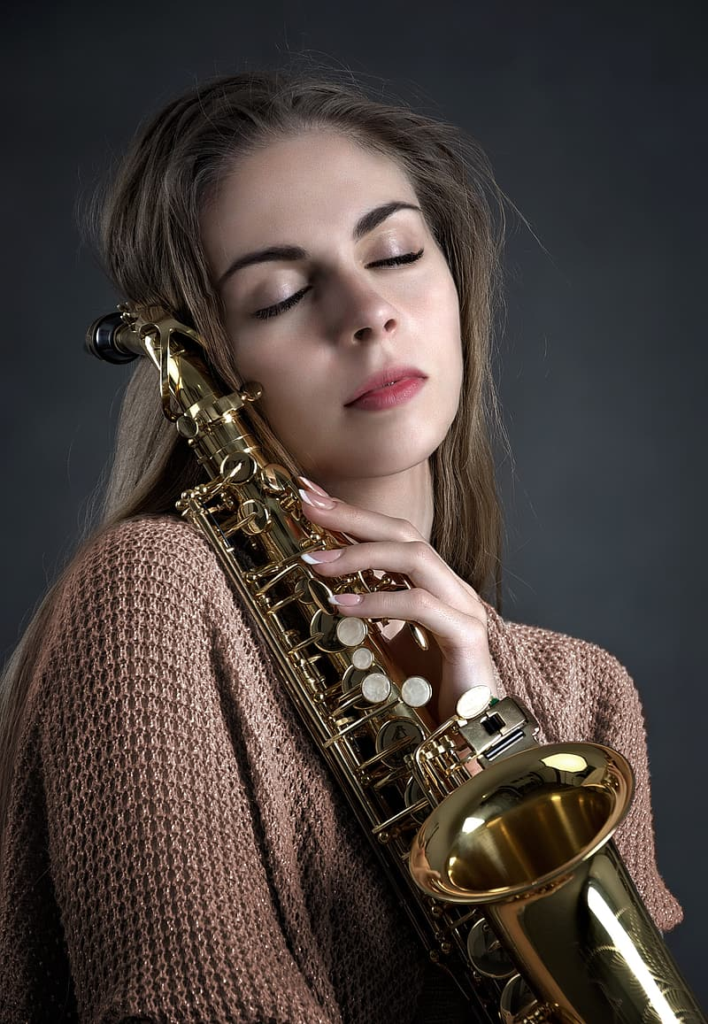Woman holding brass-colored saxophone