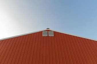 Orange and white painted barn over blue and cloudy sky at daytime