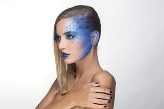 Woman wearing blue lipstick and blue polka-dotted design the left side of her face