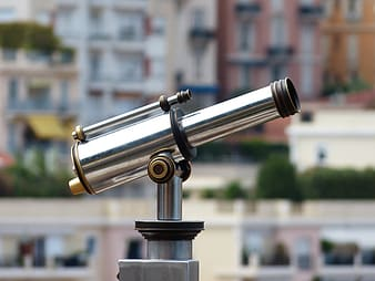 Person taking photo of stainless steel coin generated telescope in tilt shift photography