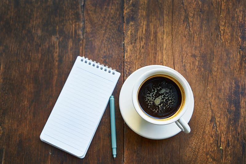 Cup of coffee on saucer beside notebook and pen