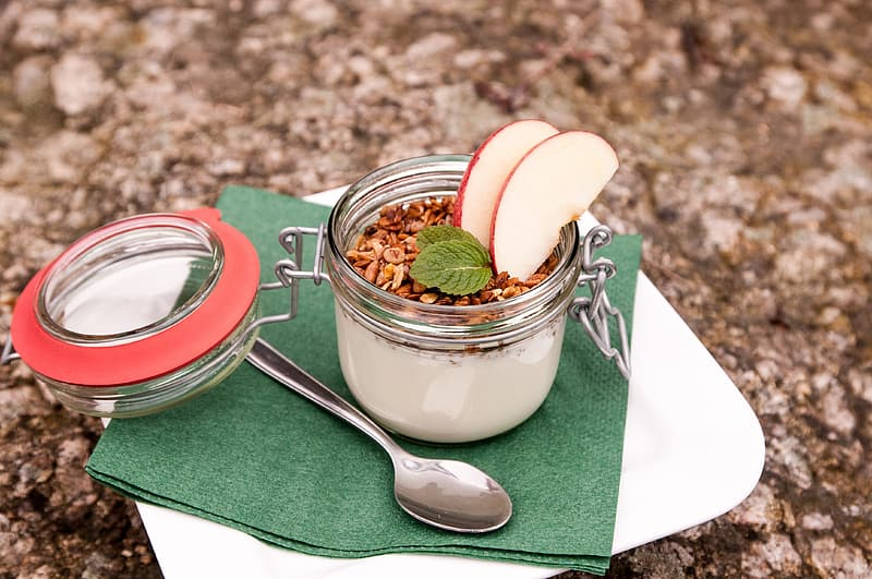 Cereal with milk and apple slice in clear glass canister