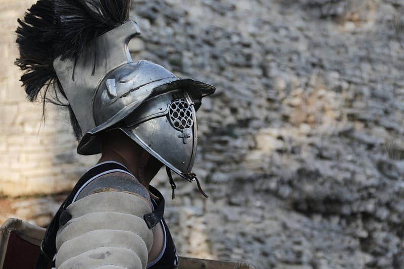 Man with soldier helmet near the gray cliff photo