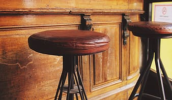 Two round brown padded stool chairs