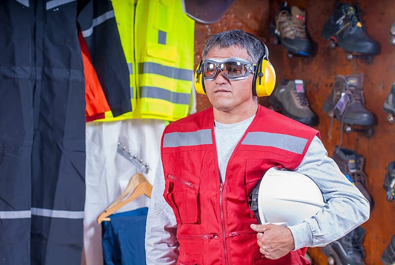 Man wearing red zip up vest carrying white hardhat