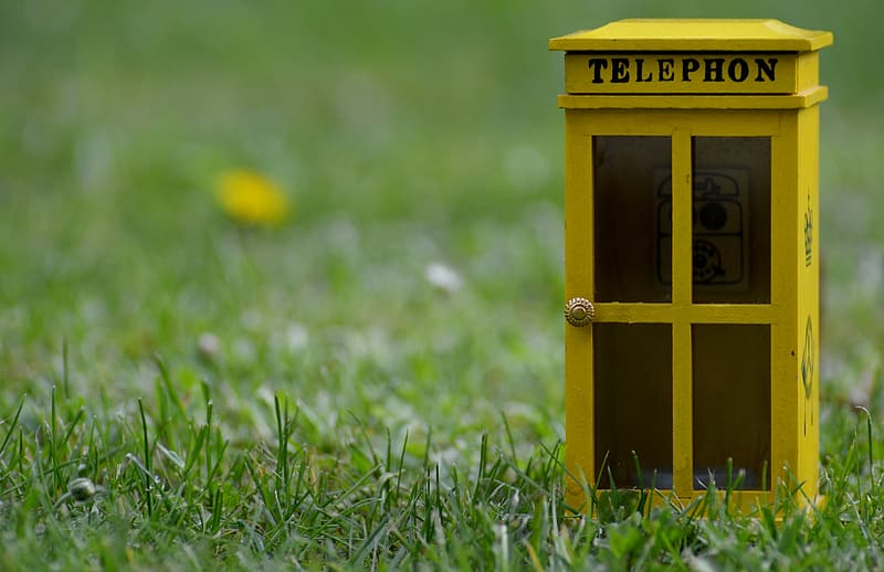 Yellow telephone booth on green grass