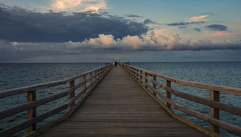 Brown wooden dock on sea under white clouds and blue sky during daytime
