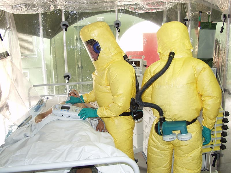 Man in yellow jacket lying on hospital bed