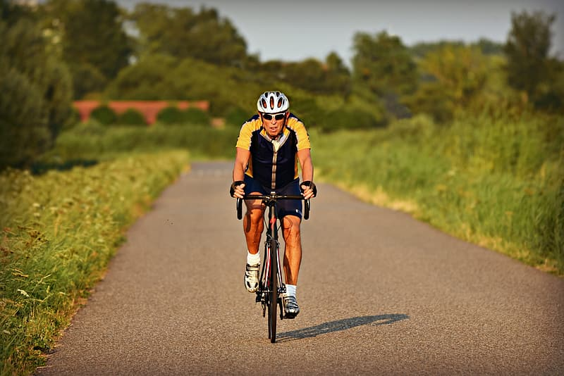Man in black and white bicycle helmet riding bicycle on gray asphalt road during daytime