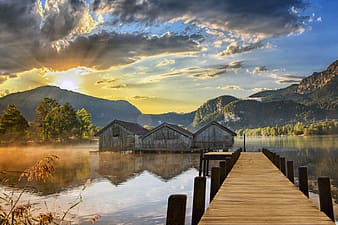 Brown wooden dock on lake near green trees and mountains under white clouds and blue sky