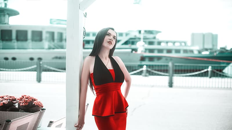 Woman wears red and black sleeveless dress