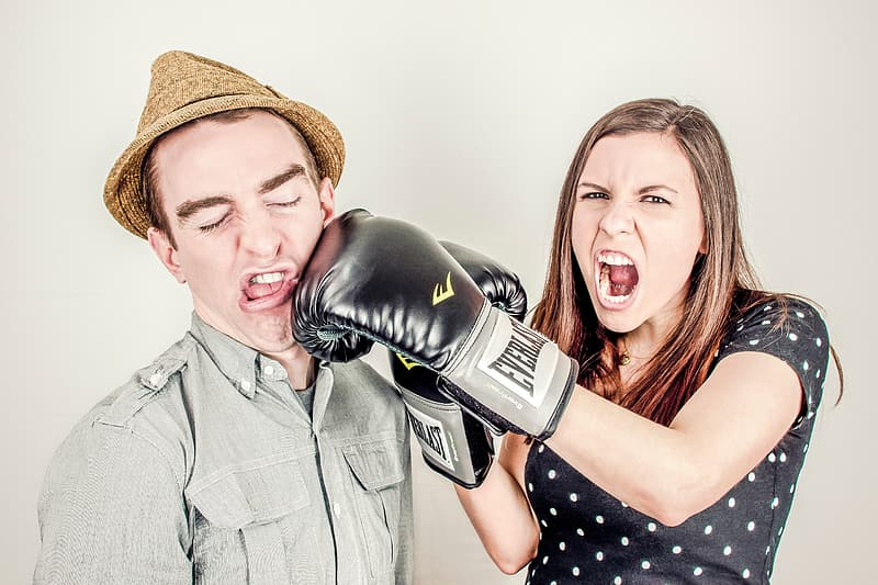 Woman wearing black Everlast boxing gloves beside man wearing brown fedora hat