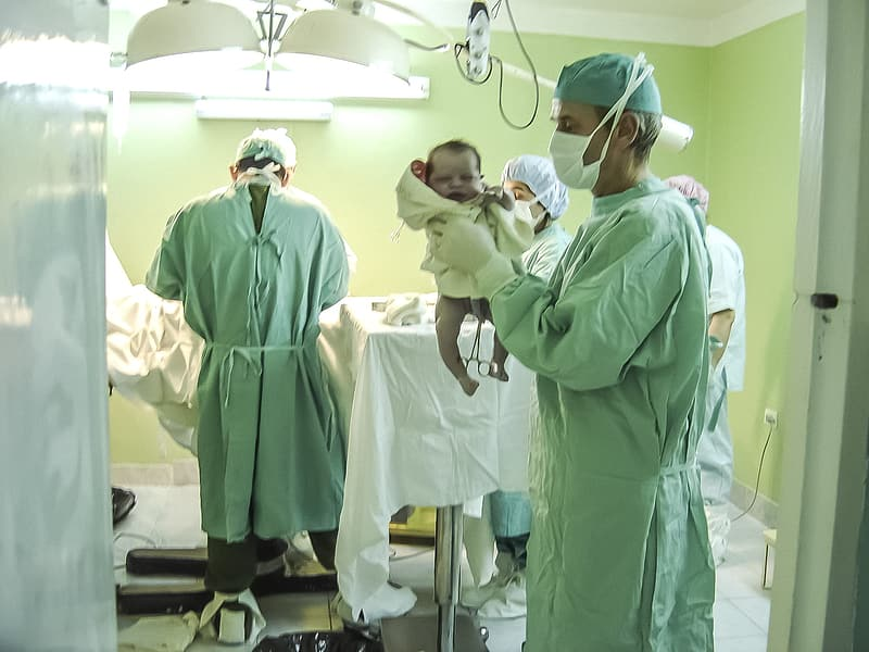 Man holding baby inside room with doctor