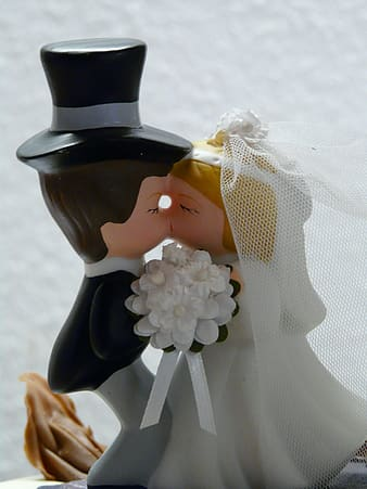 Man and woman kissing figurine near white wal
