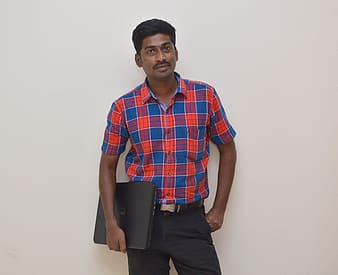 Man holding black laptop computer while standing near white painted wall