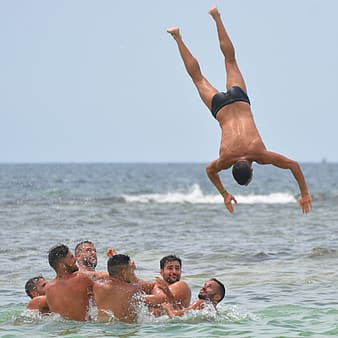 Man flipping over sea