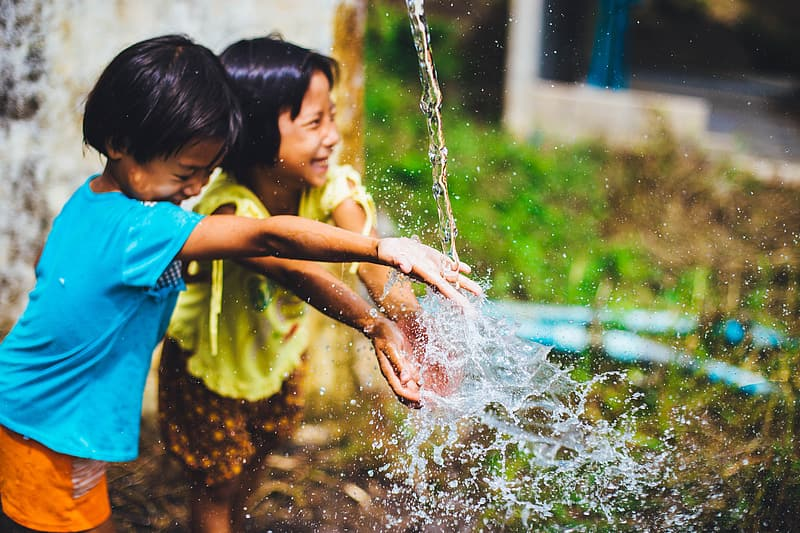 Two girls playing water while standing during daytime