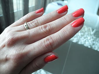 Person showing red manicure