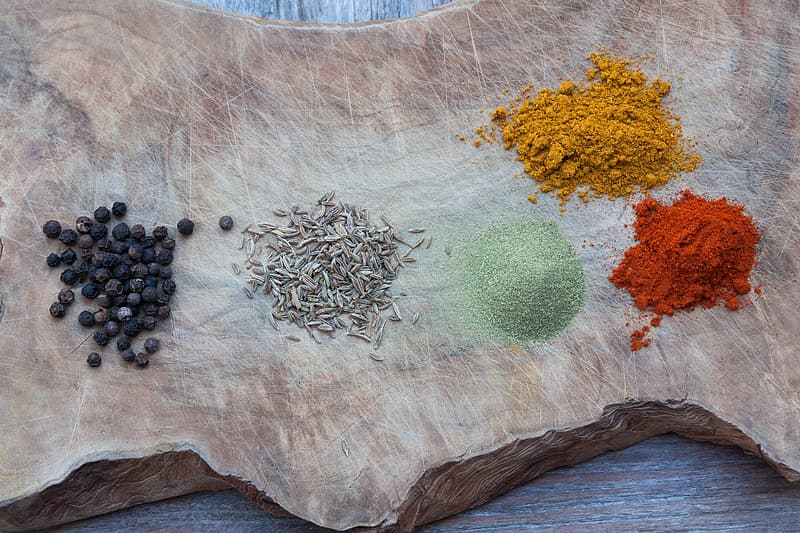 Five assorted spices on wood slab
