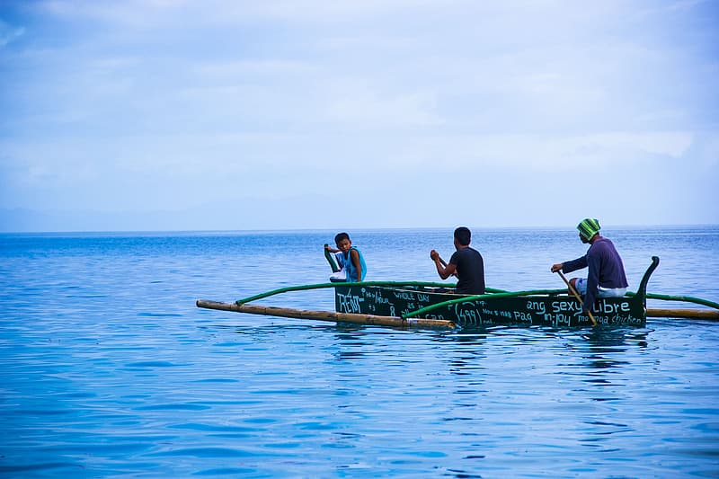 Three man on boat in the middle on calm blue sea under blue sky