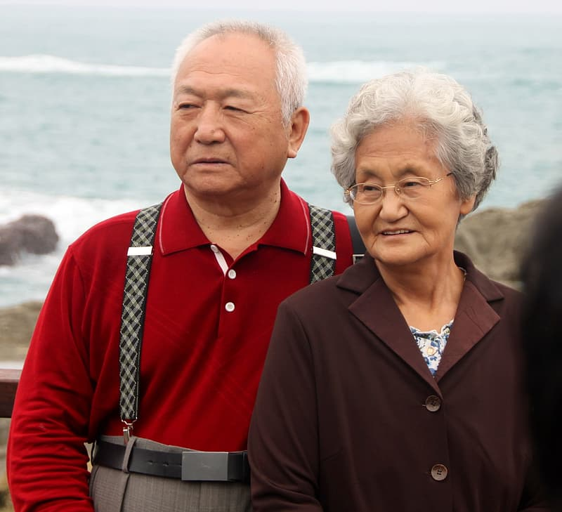 Woman in brown coat in front of man in red polo shirt near body of water