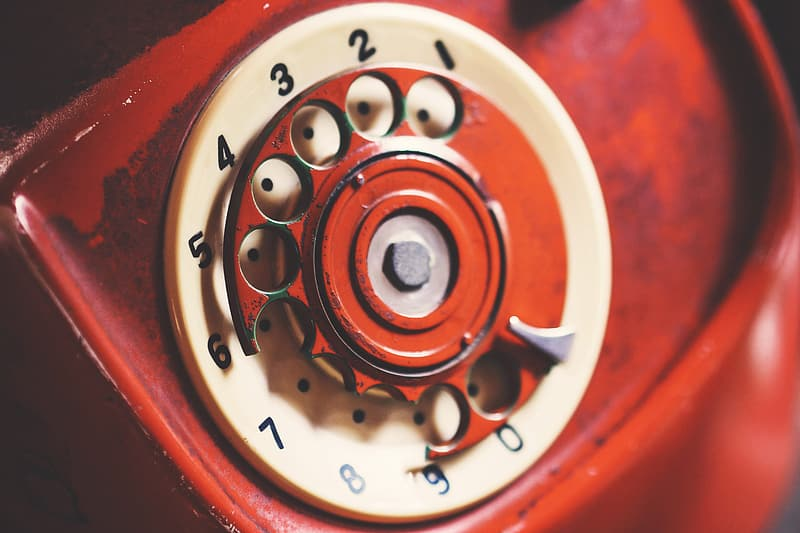 Red and white rotary phone selective focus photography