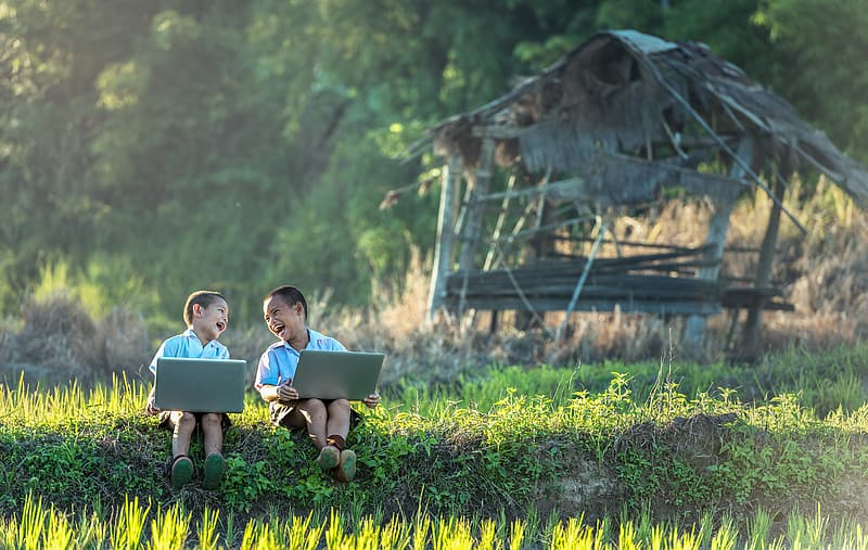 Two toddlers sitting on grass field while holding gray laptops