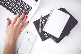Silver iPhone 6 near notebook, pen, wallet and white and black laptop computer
