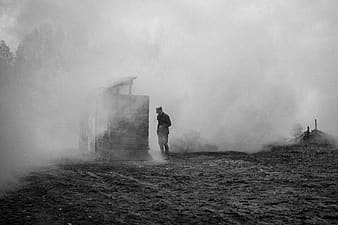 Grayscale photography of a man standing next to wooden house with smokes